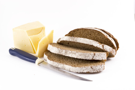 Sliced brown loaf of bread with a knife and cut cheese slices photo