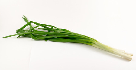 bases: Three fresh green spring onions on a white background with green leaves and white bases Stock Photo