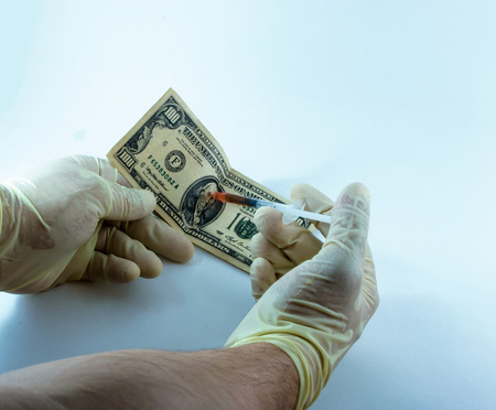 hypodermic needles: A latex gloved stranger injects a hundred dollar bill with a stimulant designed to grow the economy