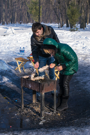 russian man: UFABASHKORTOSTAN RUSSIA - 7th March 2015 - A Russian man and wife enjoy a shashlik barbecue in the winter snow