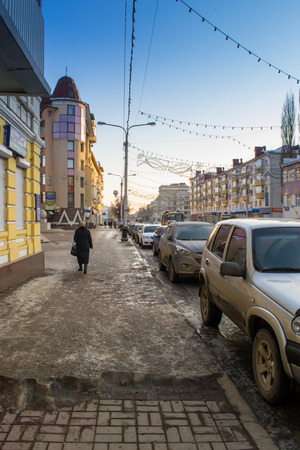 fanghiglia: A quite urban winter street scene with melting snow, ice and slush