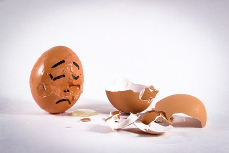 A sad egg with a face cries over the broken egg shells of a friend photo