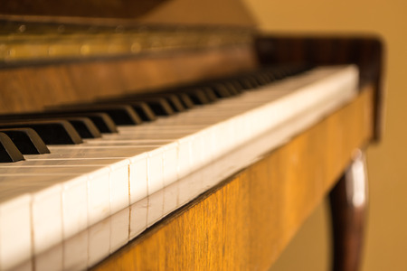 upright piano: Old upright piano with keys and dark wood construction