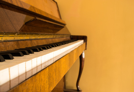 upright piano: An antique upright piano with white keys and copyspace