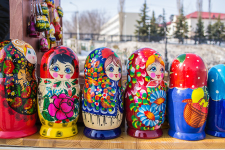 Different nesting dolls in painted wood form a line photo
