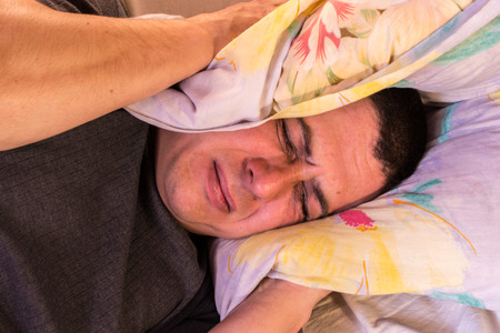 A man feels the effect of noisy neighbours as he tries to sleep photo