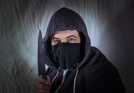 menace: A masked intruder with a kitchen knife glares with menace