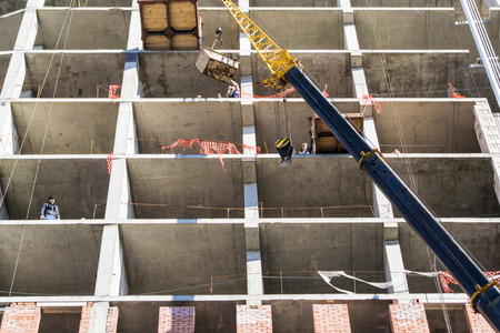 17th of march: UFABASHKORTOSTAN - RUSSIA - 17th March 2015 - Construction workers await a delivery of concrete before commencing building work on a new office block in the city center