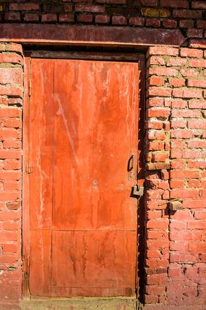 metal door: Metal door in red with a lock framed by a red brick wall