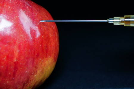 hypodermic needle: Hypodermic Needle injects a red apple with a brown liquid