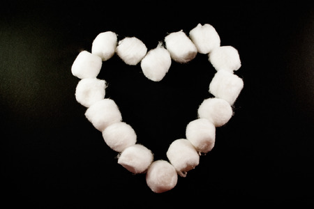 A single white cotton bud heart on a grey background Stock Photo