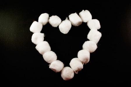A single white cotton bud heart on a grey background Reklamní fotografie