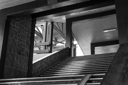 expressionism: Covered walkway with steps leading to the main area in black and white Stock Photo