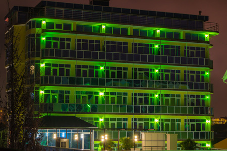 nightime: Green lit building at nightime with reflected glass and no clouds or people Stock Photo