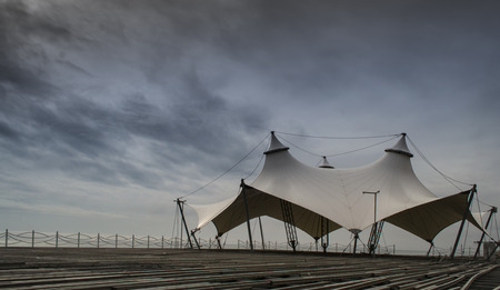 fencing wire: An empty pavilion with no people set underneath a cloudy sky