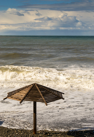 stoney: Murky waves roll onto a stoney beach and a deserted sun parasol