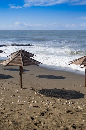 murky: Murky waves roll onto a brown sand beach and deserted wooden sun parasols