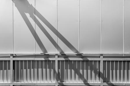 struts: Falling strut shadows cast on metal hand railings Stock Photo