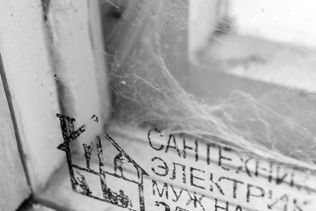 cobwebs: Cobwebs and Russian Cyrillic text in a white wooden window frame