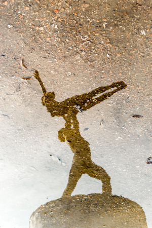 Man and Woman ballet dancers in stone reflected on water