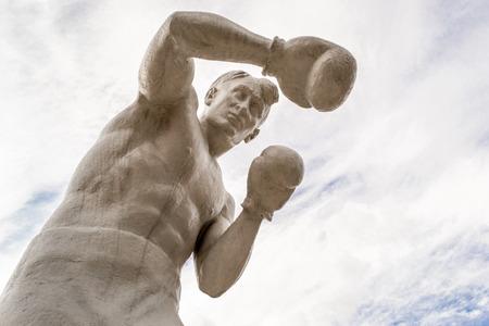 agachado: Hombre boxeador estatua con guantes de tirar golpes