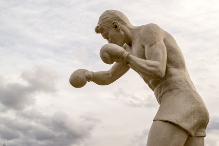 figuring: Male statue boxer with gloves throwing punches at clouds
