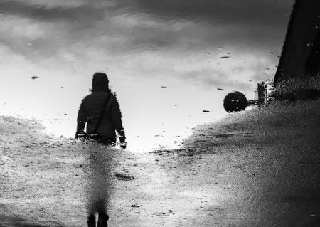 grimy: Woman walking art abstract reflection pool pond puddle rain water grey black white darkened abstract conceptual idea confusing topsy turvy spilling grimy grunge thought urban city hazard
