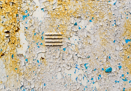 crust crusty: White paint on metal with cracks and flakes revealing a bright blue undercoat