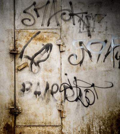scrawl: City street paint in black on grey rusted metal with a locked door in rust