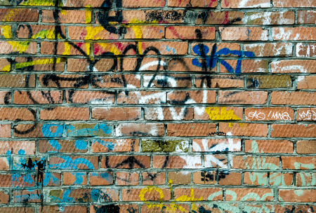 redstone: Innercity red brick wall with multicolored tags and scrawls in spray can form