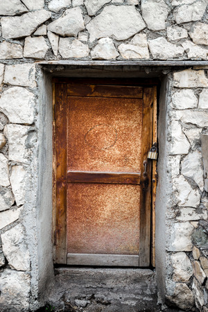 padlocked: A padlocked wooden door surrounded by grey rock and cement