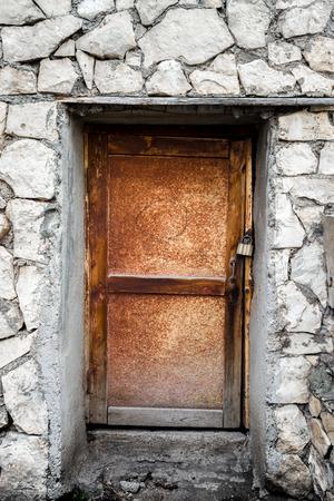 no entrance: Una puerta de madera cerrada con candado rodeado de roca gris y cemento