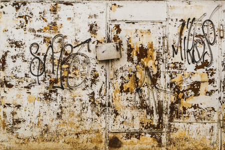 scrawl: Spary painted tags on grey metal with rust and a locked secure door entrance