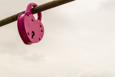 Locked pink painted padlock on an iron rod with visible keyhole photo