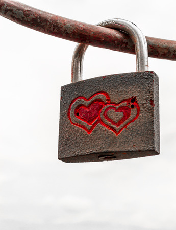interconnected: Locked padlock on iron rod with red engraved interconnected love hearts