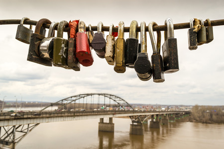 interlinked: A row of assorted locked padlocks on a secure steel rod with a traffic bridge in the background