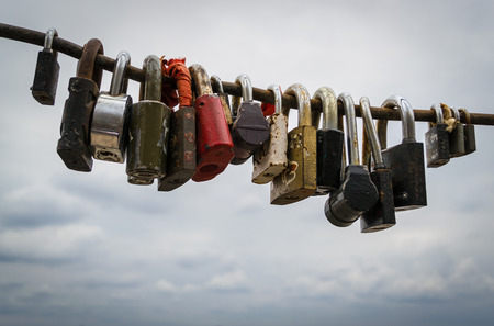 Various locked steel padlocks on a secure tough iron rod against a cloudy sky