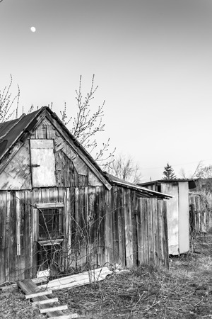 outhouse: Moon shining over a wooden rustic village shed with outhouse and moon in a cloudless sky Stock Photo