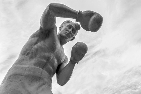 agachado: Hombre boxeador estatua con guantes de lanzar golpes en monocromo