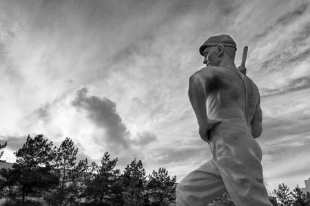 figuring: Modern industrial man in statue form striding towards the clouds in monochrome Stock Photo