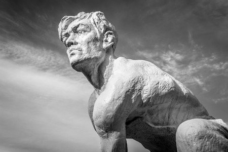 figurative: Stone body of a struggling man against a cloudy sky in monochrome