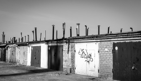 detritus: Urban city garages with chimney vents in black and white Stock Photo