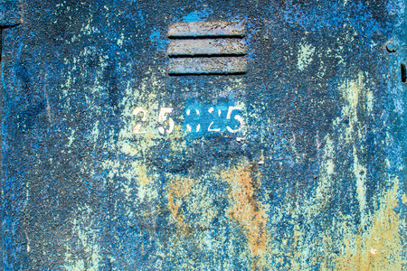 flecks: Flaking aged blue paint flecks on metal with rust and an exposed vent