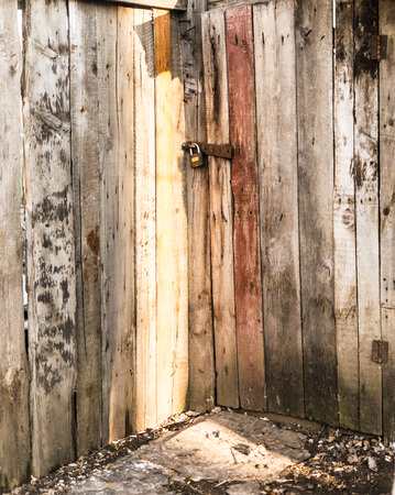 deterrence: Late evening sunlight catches a locked wooden door