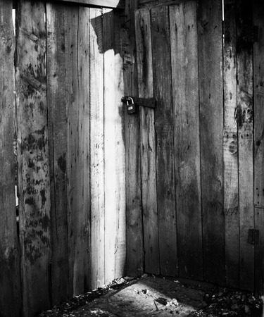 deterrence: Late evening sunlight catches a locked wooden door in black and white