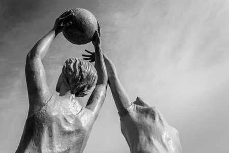 figuring: White stone statue of two women playing netball against a blue sky Stock Photo
