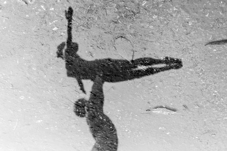 reflection: Closeup of Man and Woman ballet dancers in stone reflected on water in black and white