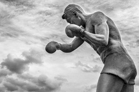 agachado: Hombre boxeador estatua con guantes de lanzar golpes en las nubes en blanco y negro Foto de archivo