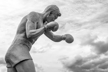 agachado: Hombre boxeador estatua lanzando golpes con guantes en las nubes en blanco y negro