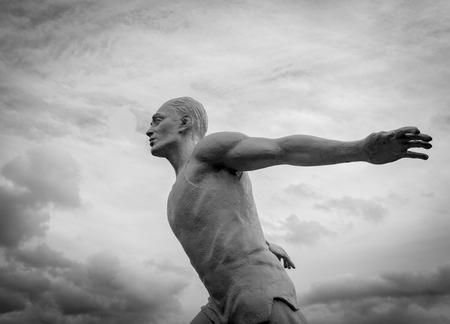 figuring: White stone statue of a man running in the clouds in monochrome black and white Stock Photo